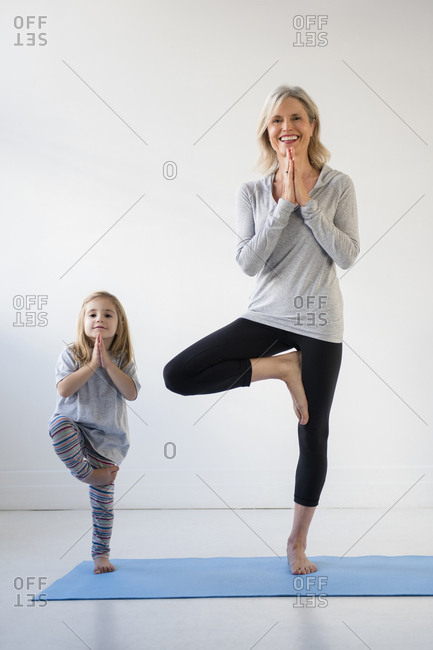 Caucasian granddaughter imitating grandmother practicing yoga