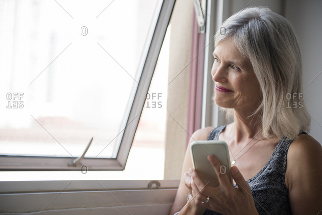 Smiling Caucasian woman texting on cell phone near window
