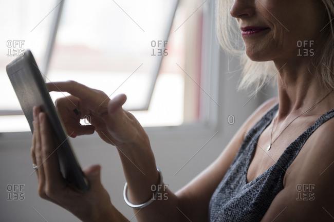 Caucasian woman using digital tablet near window