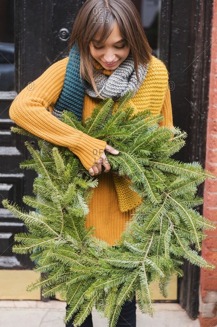 Mixed Race woman carrying pine wreath outdoors