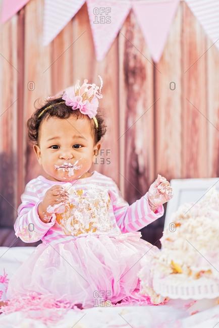 Messy Mixed Race baby eating birthday cake