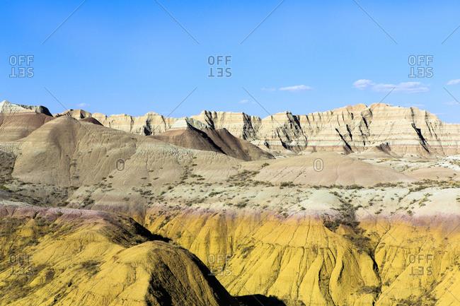 Layered rock formations under blue sky, Badlands National Park, South Dakota, United States