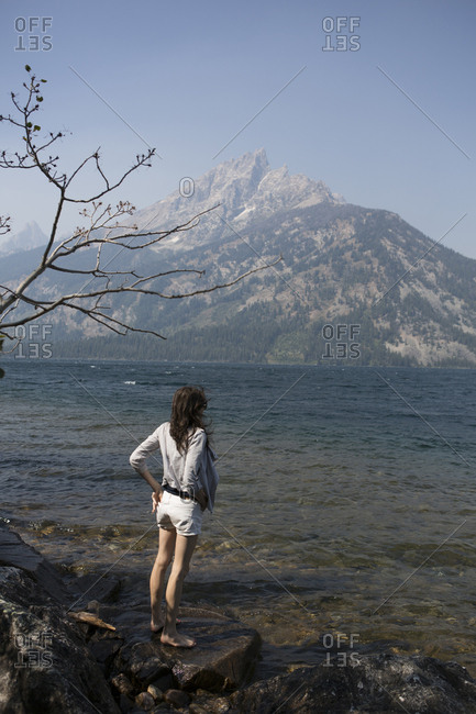 Caucasian woman standing in Jenny Lake admiring Great Teton mountains, Wyoming, United States