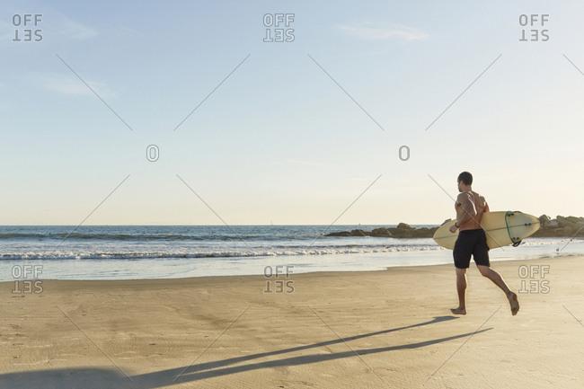 Mixed race man running with surfboard on beach