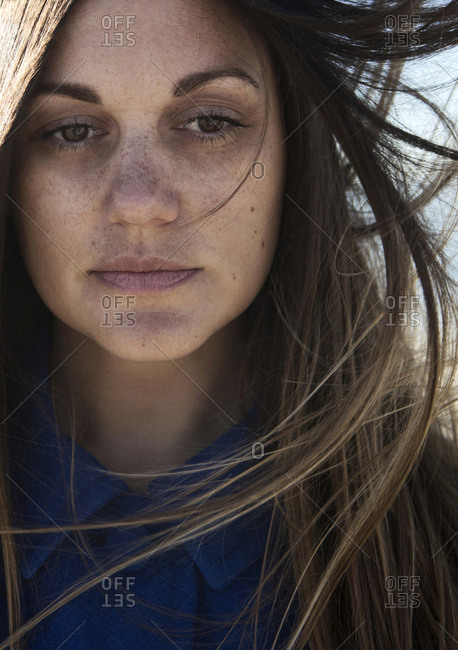 Wind blowing hair of Caucasian woman with freckles