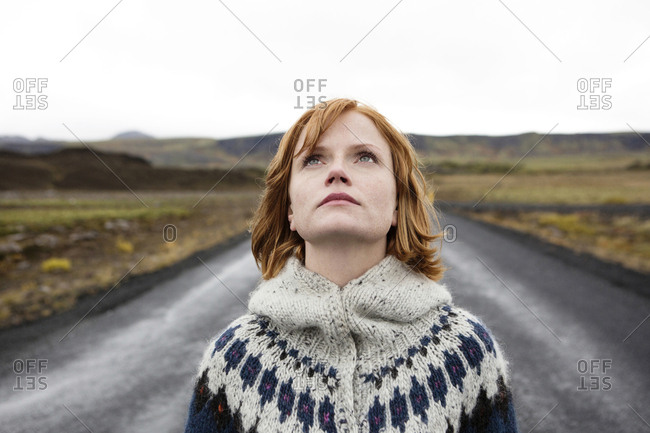 Caucasian woman wearing sweater in road looking up