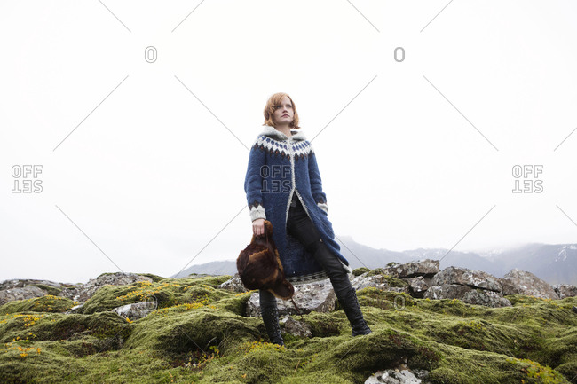 Caucasian woman standing on mossy rocks holding fur hat