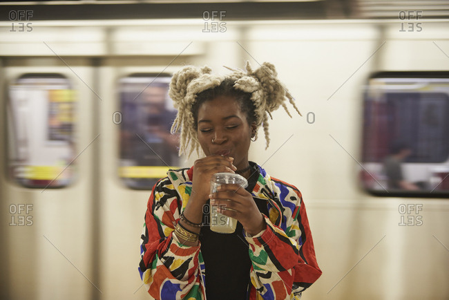 Black woman drinking from cup near subway