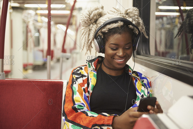 Black woman listening to cell phone with headphones on subway