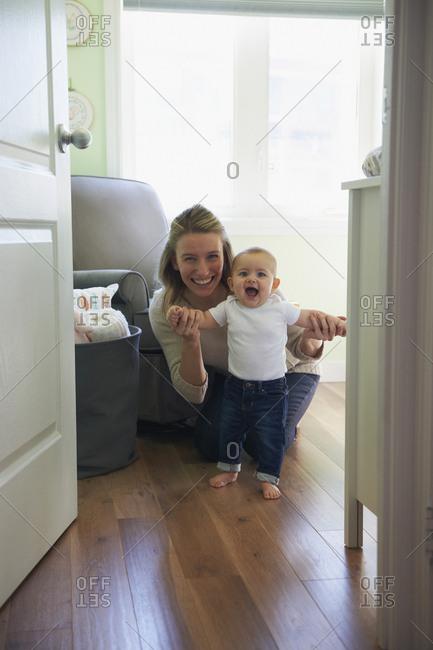Caucasian mother helping standing baby daughter