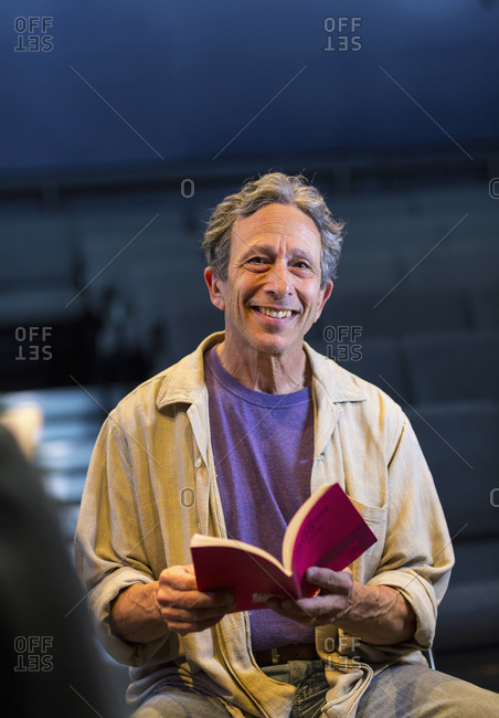 Portrait of smiling Caucasian actor holding script in theater