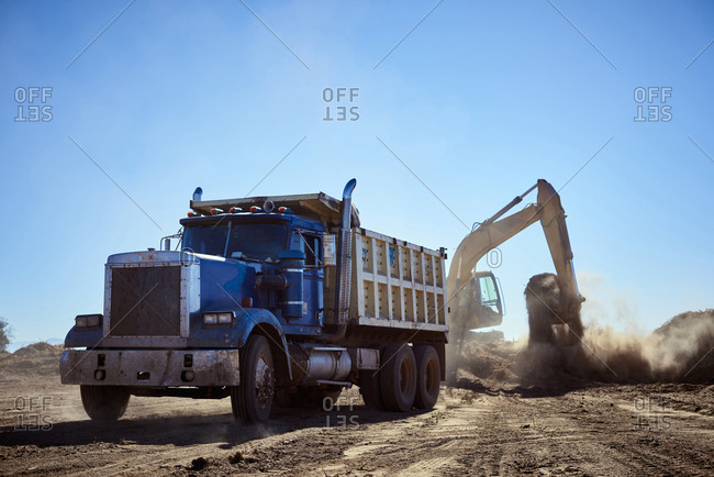 Truck near digger in dirt field