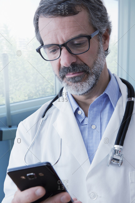 Hispanic doctor texting on cell phone