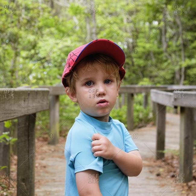 Caucasian boy scratching shoulder in park