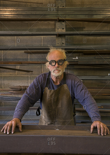 Portrait of serious Caucasian blacksmith in workshop