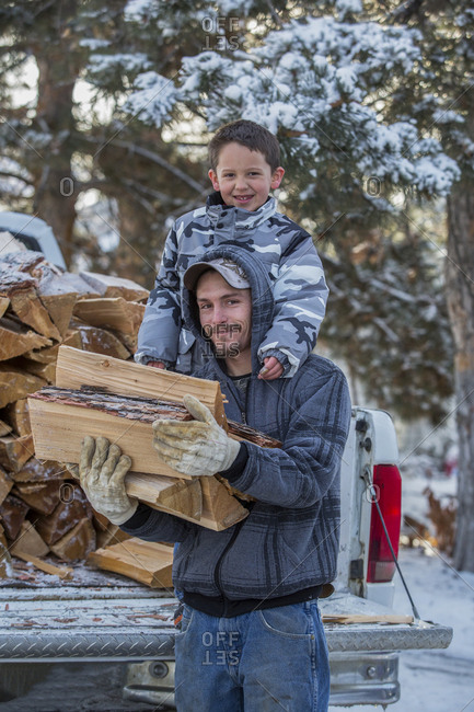 Caucasian father and son carrying firewood from truck