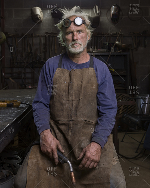 Portrait of serious Caucasian blacksmith in workshop holding torch