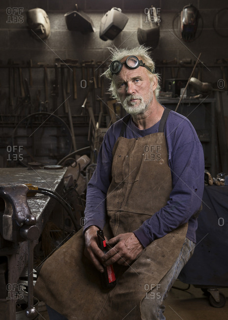 Portrait of serious Caucasian blacksmith in workshop drinking beer