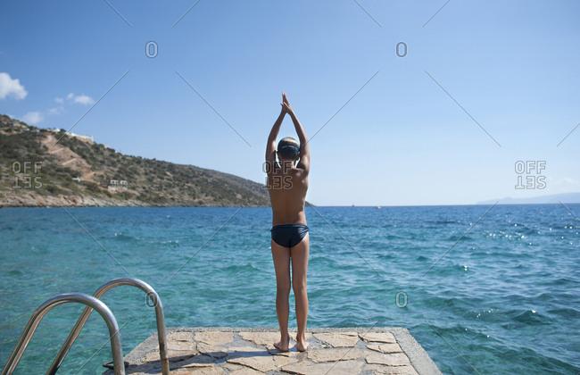 Caucasian boy preparing to swim in lake