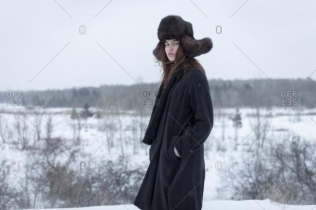 Serious Caucasian woman wearing fur hat and coat in winter