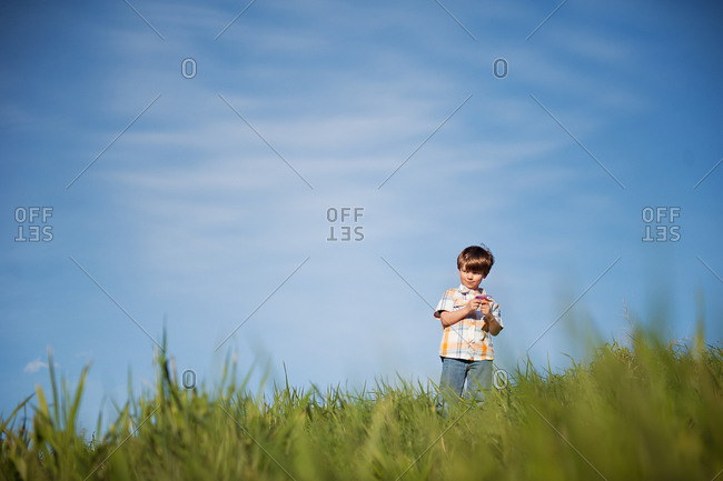 Low angle view of young boy standing in green grass