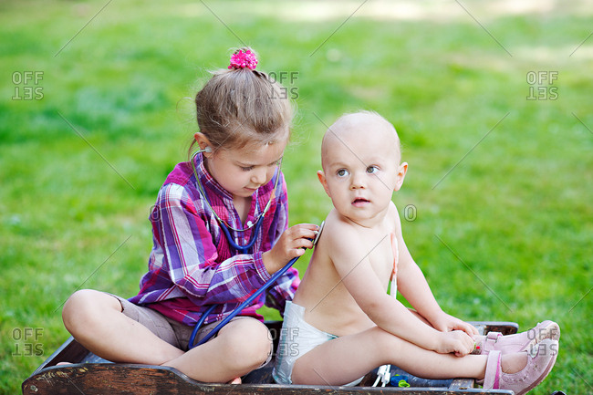 Young girl with stethoscope listens to her sister's breathing
