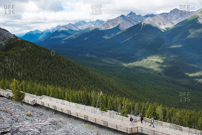 Hikers on boardwalk above a valley