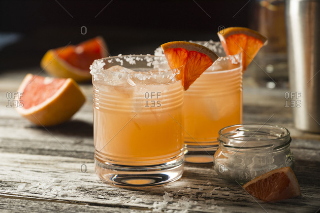 Two glasses of mixed drinks served with oranges