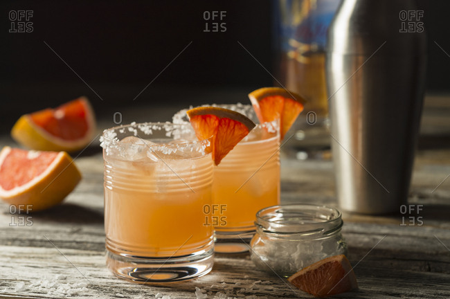 Two glasses of mixed drinks served with oranges on table with cocktail shaker