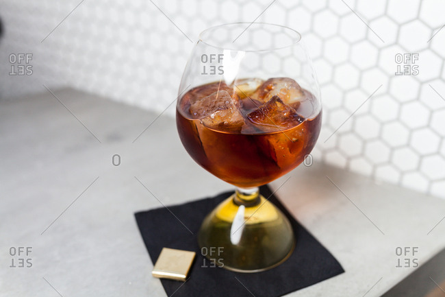 Dark alcoholic drink served in a glass with ice cubes