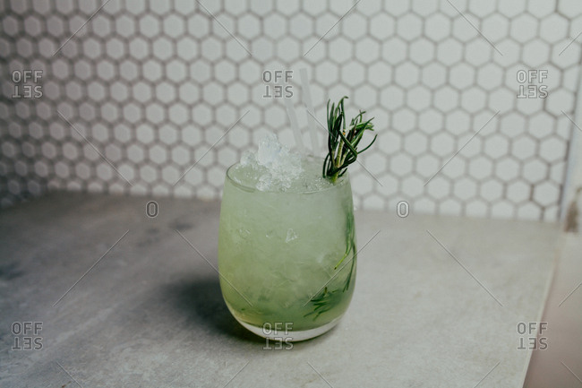 Mixed drink garnished with a sprig of fresh herbs