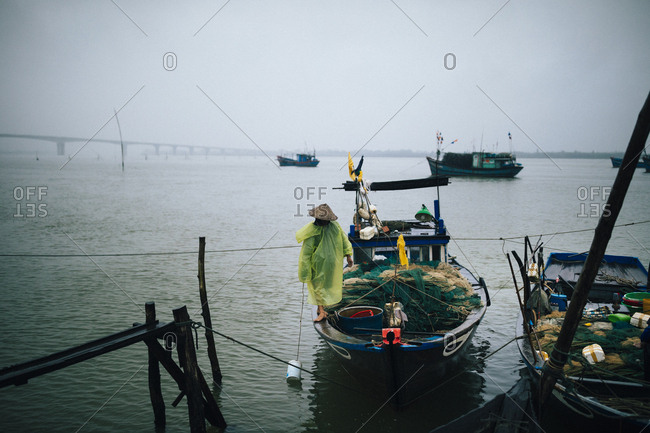 A fisherman on his boat during an early morning rain shower in Hoi An, Vietnam.