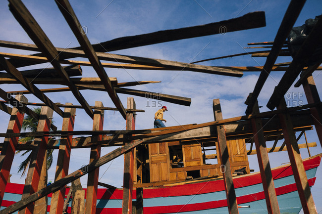 Hoi An, Vietnam - January 16, 2017: Men at work at a shipyard in central Vietnam, getting boats ready for the sea.