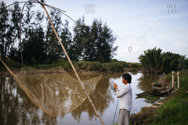 Hoi An, Vietnam - January 16, 2017: A young man catches fish along a small river in Hoi An, Vietnam.