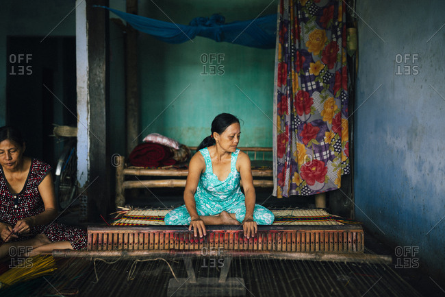 Hoi An, Vietnam - January 16, 2017: A woman weaves bamboo rugs in a small rural village in central Vietnam.