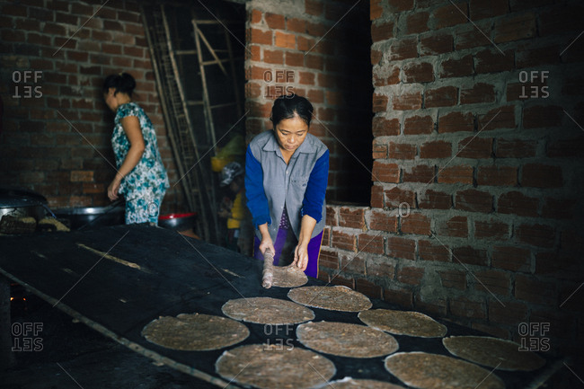 Hoi An, Vietnam - January 16, 2017: Women make rice pancakes at a small village house in the Hoi An countryside, in central Vietnam.
