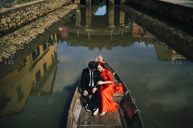 Hoi An, Vietnam - January 17, 2017: Vietnamese newlyweds have their photo taken in a small boat with the historic Japanese covered bridge reflected behind them in Hoi An, Vietnam.
