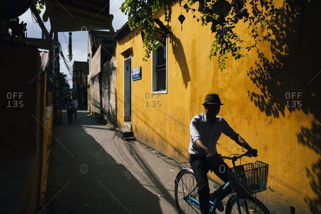 Hoi An, Vietnam - January 17, 2017: A man rides his bicycle down the old streets of Hoi An in central Vietnam.
