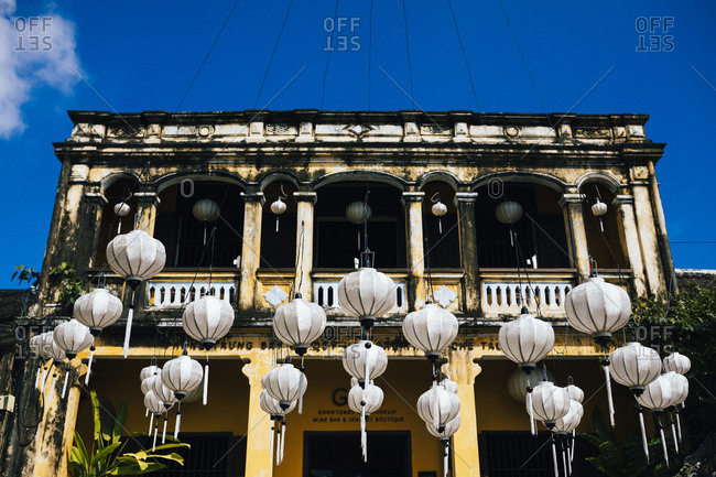 Hoi An, Vietnam - January 17, 2017: Lanterns hang in front of an historic building in downtown Hoi An, Vietnam.