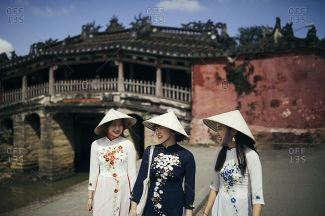 Hoi An, Vietnam - January 17, 2017: Three tourists walk around the Old Town of Hoi An, Vietnam wearing traditional dresses.