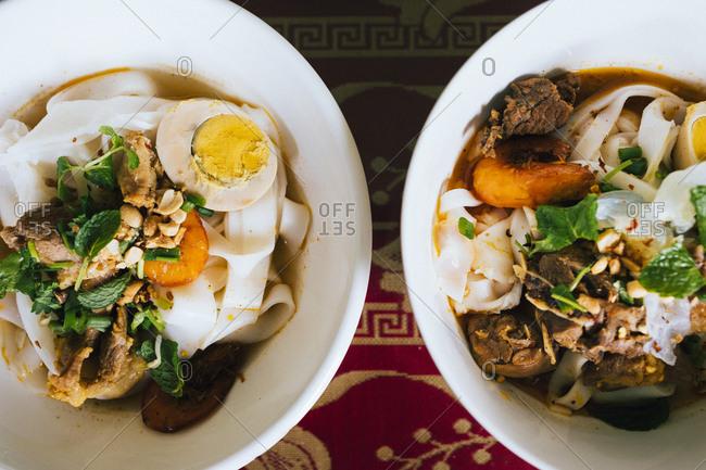 Bowls of Mi Quang noodles with pork and shrimp in Danang, Vietnam.