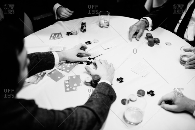 Saint Paul, Minnesota - 1/30/2016: Four people sitting around a table playing poker
