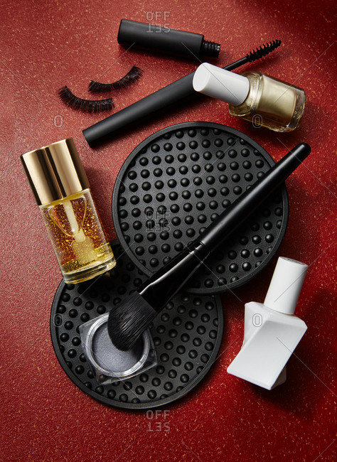 Cosmetics arranged on red background
