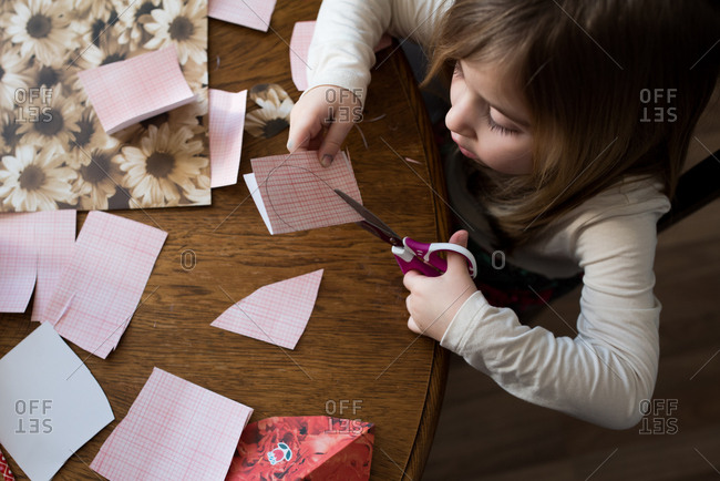 Overhead view of young girl cutting hearts out of paper