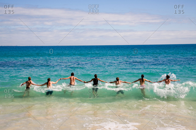 Many people holding hands wading in the ocean as waves break around them on Cottesloe Beach in Perth, Western Australia