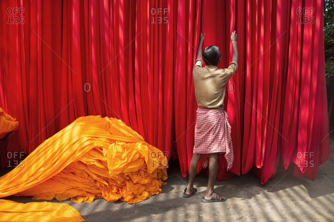 Man adjusting freshly dyed cloth now drying in Jaipur, India