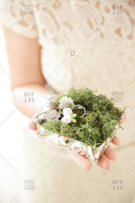 Bride holding ring in moss