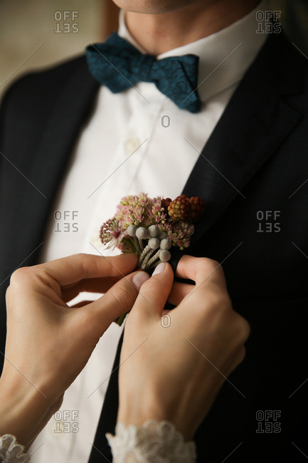 Woman putting boutonniere on groom