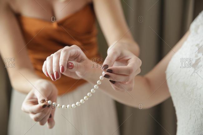 Woman putting bracelet on bride
