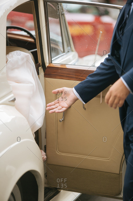 Groom giving hand to bride in car